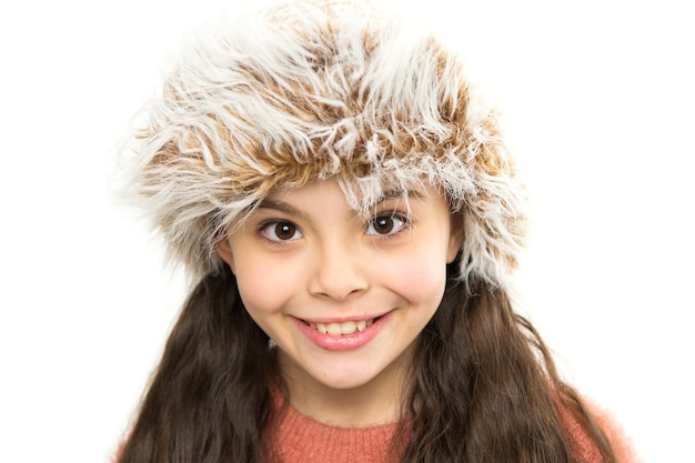 Ausgefallenes fell. kuscheliges winteroutfit. kleinkind trägt hut. bleiben sie diesen winter warm. glückliches kleines mädchen in wintermode. kleines kind, das im weißen hintergrund der pelzmütze lächelt. nettes modell genießen winterstil.