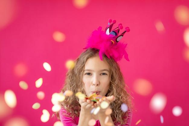 Ausgefallenes mädchen bläst konfetti gegen rosa bakground fröhliches kind, das spaß am karneval-mardi-gras-feiertagskonzept hat