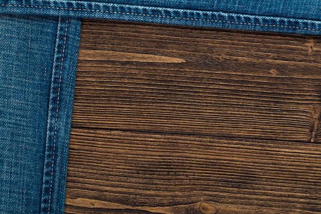 Ausgefranste jeans oder blue jeans-denim-kollektion auf rauem dunklem holz
