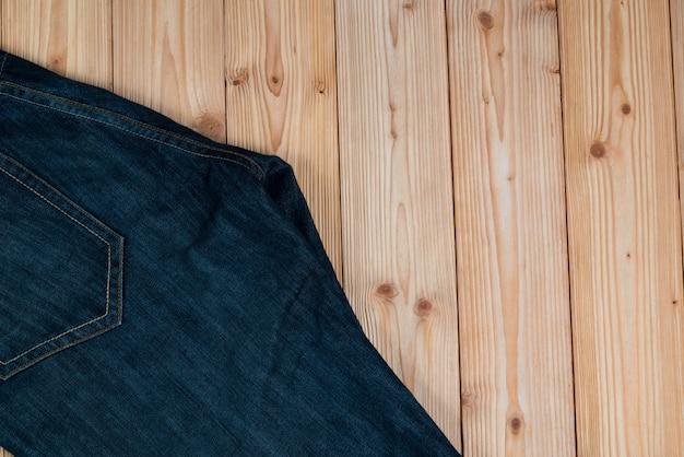 Ausgefranste jeans oder blue jeans denimsammlung auf holz