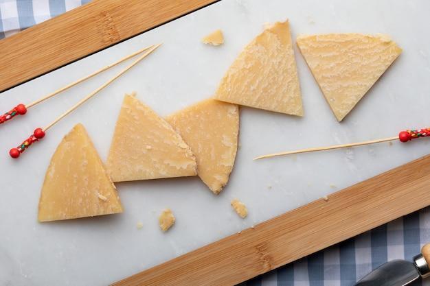 Ausgehärteter schafskäse. auf weißem marmor und brot in stücke schneiden. zahnstocher für käse. draufsicht.