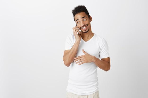 Ausgehender hübscher schwarzer mann im weißen t-shirt, der am telefon spricht, lächelnd, glückliches gespräch