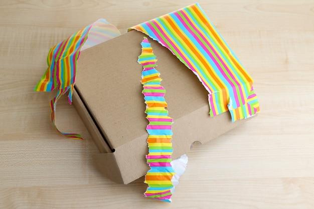 Ausgepackte und geöffnete geschenkbox auf holzoberfläche