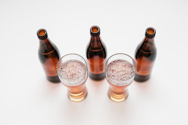 Ausgerichtete bierflaschen und gläser auf weißem hintergrund