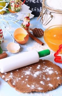 Ausgerollter teig für lebkuchen weihnachtsselbst gemachte kuchen auf einer rustikalen art der hellen hölzernen hintergrundselektiven weichzeichnung