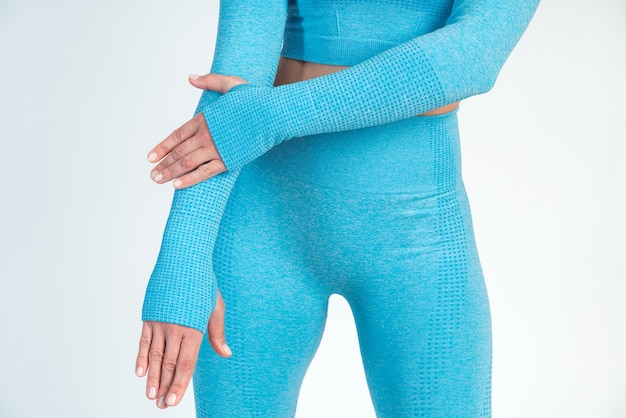 Ausgeschnittene ansicht der starken frau mit abgeschnittenem oberteil und leggings, die isoliert auf weißem hintergrund steht und posiert. sportliches auftrittskonzept