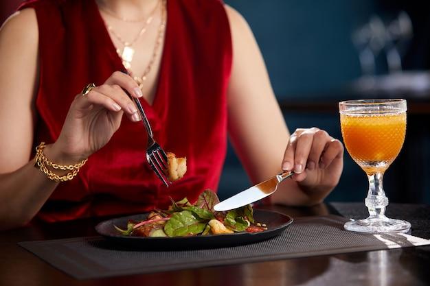 Ausgeschnittene ansicht einer frau, die frischen salat zum mittagessen im luxusrestaurant isst, gesunde lebensweise