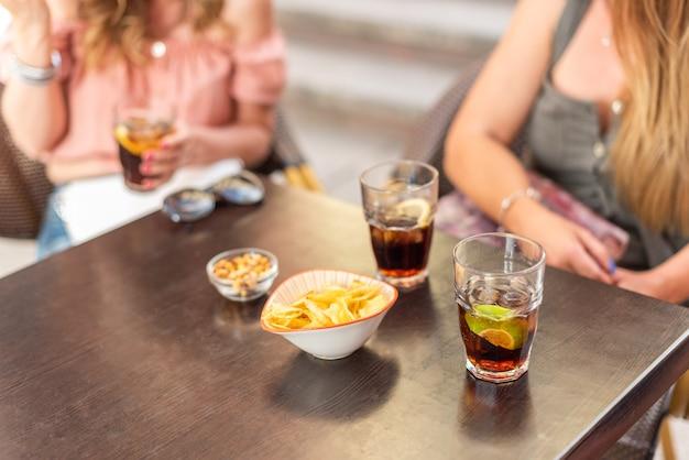 Ausgeschnittene ansicht einiger getränke und snacks, die von erwachsenen freunden konsumiert werden. reife frauen, die eine gute zeit zusammen haben.