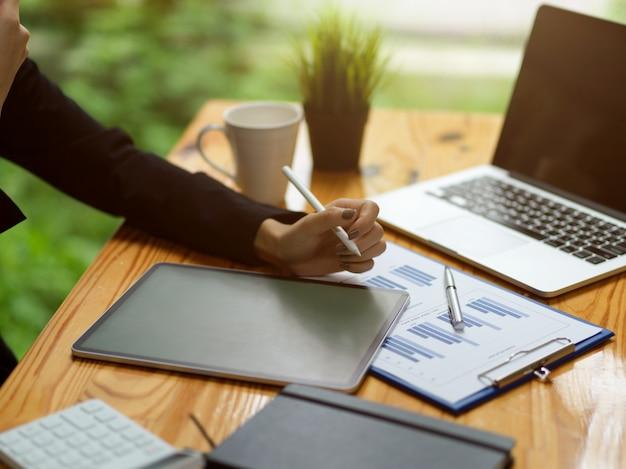 Ausgeschnittene aufnahme der weiblichen hand mit einem intelligenten digitalen tablet mit finanzberichtsgrafik