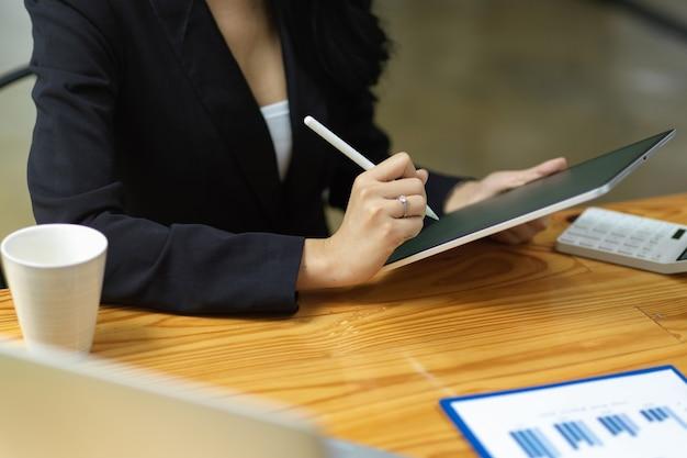 Ausgeschnittene aufnahme einer geschäftsfrau im schwarzen anzug, die auf einem smart-tablet mit einem holzschreibtisch mit einem stylus schreibt