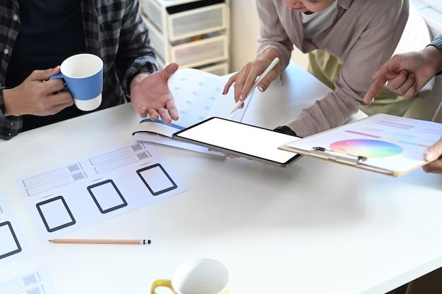 Ausgeschnittene aufnahme eines designerteams mit digitalem tablet und brainstorming über farbdesign in der designagentur.