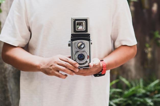 Ausgeschnittene aufnahme eines mannes, der eine analoge vintage-kamera hält