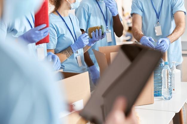 Ausgeschnittene aufnahme von freiwilligen in blauen einheitlichen schutzmasken und handschuhen, die lebensmittel verpacken und
