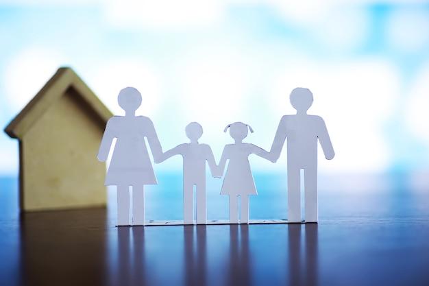 Ausgeschnittene papierkettenfamilie mit schutz der hohlen hände, konzept für sicherheit und pflege. hände mit ausgeschnittener papiersilhouette auf dem tisch. familienbetreuungskonzept