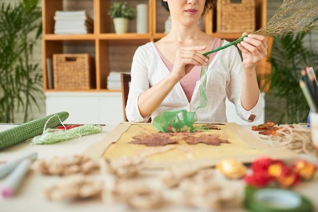 Ausgeschnittenes bild einer jungen frau, die getrocknete wildblumen mit grünem nylonband dekoriert