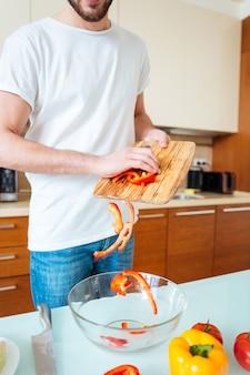 Ausgeschnittenes bild eines mannes, der in der küche salat macht