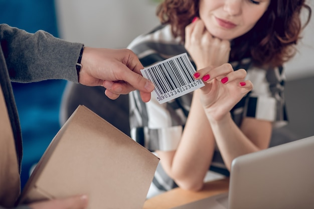 Ausgeschnittenes foto einer frau, die ihrem männlichen kollegen ein barcode-etikett mit einem karton überreicht