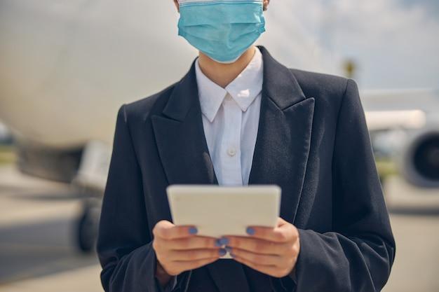 Ausgeschnittenes foto einer frau in einer schutzmaske, die ihren tablet-computer mit zwei händen hält