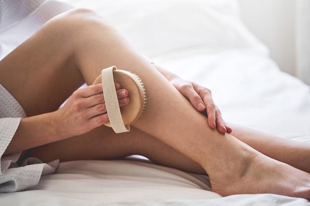 Ausgeschnittenes foto einer jungen kaukasischen frau, die lymphdrainage mit einer badebürste macht