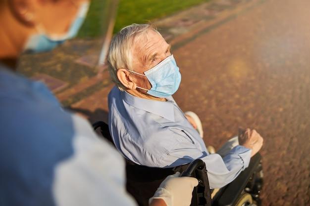 Ausgeschnittenes foto einer person, die ältere menschen im rollstuhl rollt
