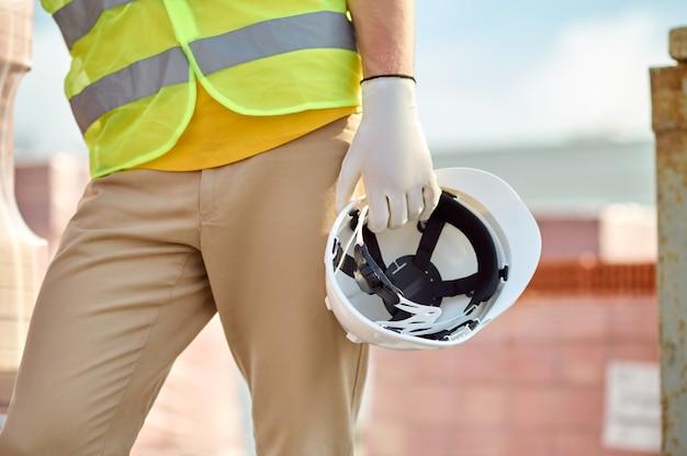 Ausgeschnittenes foto eines arbeiters in einer warnweste, der einen schutzhelm mit einer behandschuhten hand hält