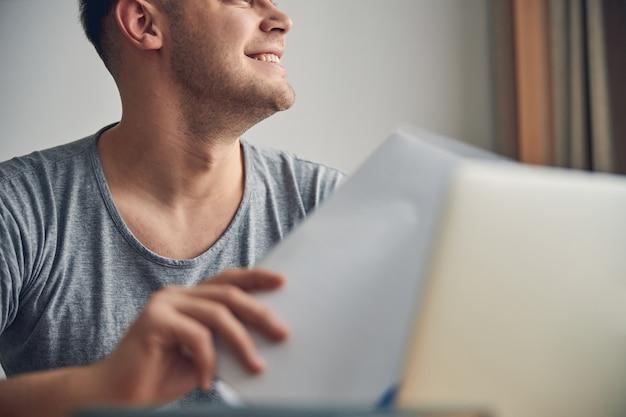 Ausgeschnittenes foto eines attraktiven kaukasischen mannes, der beim schauen und lächeln sitzt und dokumente hält