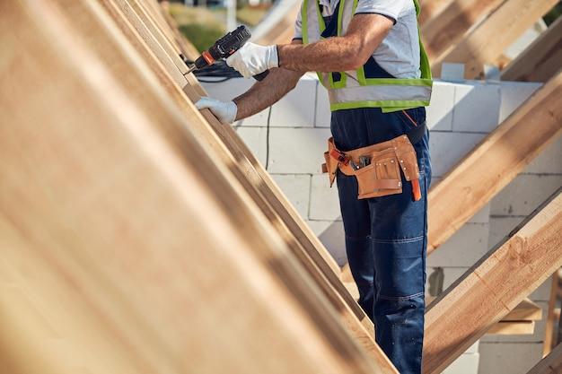Ausgeschnittenes foto eines baustellenarbeiters, der einen praktischen werkzeuggürtel trägt und in den hölzernen dachrahmen bohrt