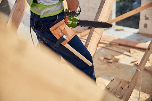Ausgeschnittenes foto eines gut ausgestatteten baumeisters, der einen werkzeuggürtel trägt, eine kettensäge hält und mit holz arbeitet