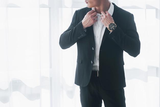 Ausgeschnittenes foto eines mannes im anzug, der an der weißen wand steht