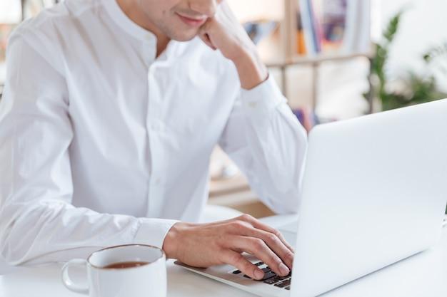 Ausgeschnittenes foto eines mannes in weißem hemd mit laptop-computer. coworking.