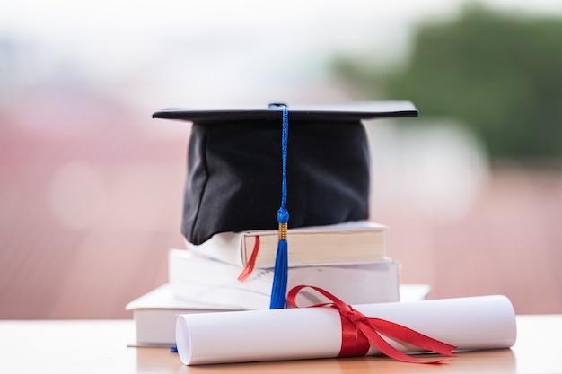 Ausgeschnittenes foto eines universitätsabschlusshutes und diplomabschlusszeugnisses auf dem tisch
