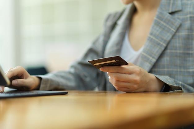 Ausgeschnittenes foto von hand, die kreditkarte hält und tablet verwendet