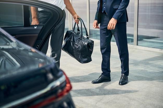 Ausgeschnittenes foto von zwei männern, die in der nähe der offenen tür eines autos stehen, bevor sie einsteigen
