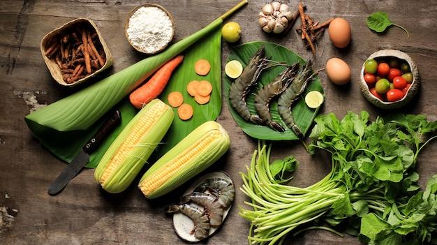 Ausgewählte focus flatlay cooking zutaten vorbereitung, zubereitung von spinatsuppe (sayur bayam) und shrimp tempura. zusammensetzung rohe frische zutaten mit kopienraum für text oder werbung