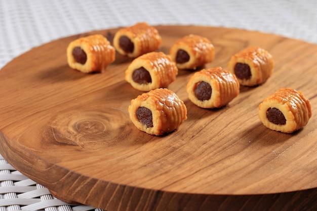Ausgewählte focus fresh baked ananas tart roll cookies (tart nanas oder kuih nenas oder nastar gulung) auf holzuntergrund. vor dem verkauf bei eid mubarak