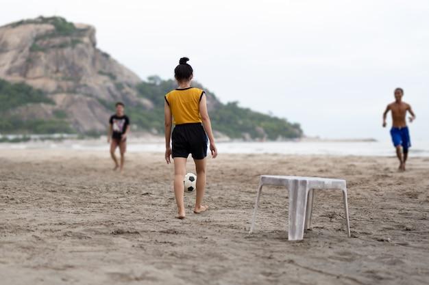 Ausgewählte fokusgruppe freunde, die fußball auf dem strand in der sommerzeit spielen.