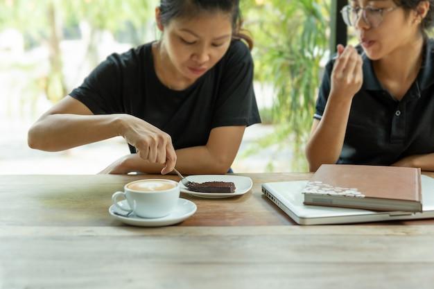 Ausgewählte freunde des foceus genießen es, schokoladenkuchen in der kaffeestube zu essen.