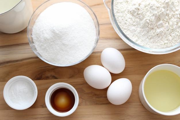 Ausgewählte zutaten: eier, zucker, milch, vanilleessenz, ferment und öl für die zubereitung eines kuchens