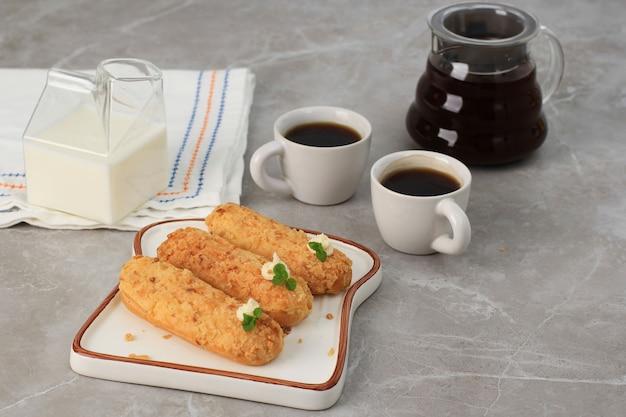 Ausgewählter focus craquelin eclair, köstliches französisches brandteig-dessert mit tigermotiven oben (craquelin), garniert mit minzblatt und sahne. serviert mit kaffee