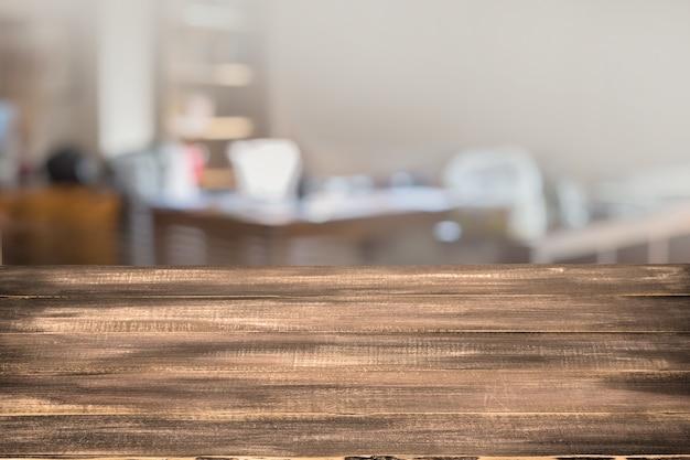 Ausgewählter fokus leerer brauner holztisch und café verwischen hintergrund mit bokeh-bild, für die montage der produktanzeige.