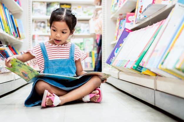 Ausgewähltes buch des netten asiatischen kindermädchens und lesen eines buches in der buchhandlung im supermarkt