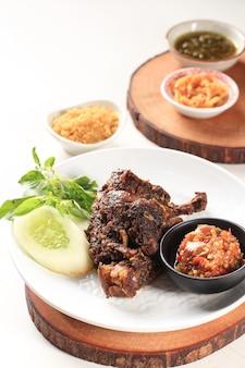 Ausgewähltes focus bebek madura, traditionelles gebratenes entenmenü auf indonesisch. populäres menü kam aus madura, ost-java. wird normalerweise mit rohem gemüse und würzigem sambal serviert. beliebt als penyetan