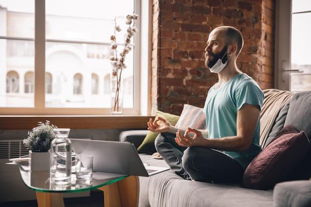 Ausgewogen. junger mann, der zu hause yoga macht, während er unter quarantäne steht und freiberuflich online arbeitet
