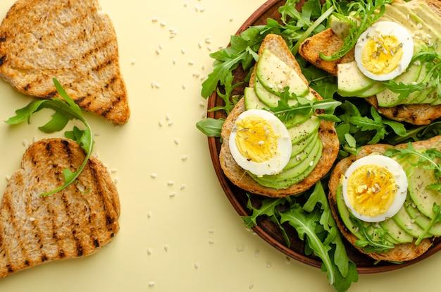 Ausgewogene ernährung. avocado toast mit ei und rucola salat. über uns flach liegen