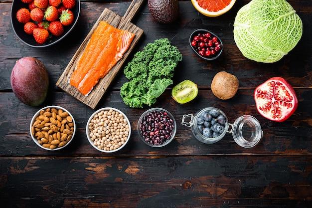 Ausgewogene ernährung bio gesunde lebensmittel saubere auswahl, flach auf dunklem holztisch liegen