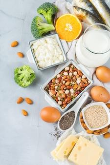 Ausgewogene ernährung, gesundes ernährungskonzept. auswahl an kalziumreichen nahrungsquellen, bohnen, milchprodukte, sardinen, brokkoli, chiasamen, mandeln auf einem küchentisch