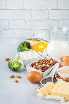 Ausgewogene ernährung, gesundes ernährungskonzept. auswahl an kalziumreichen nahrungsquellen, bohnen, milchprodukten, sardinen, brokkoli, chiasamen, mandeln auf einem küchentisch. raumhintergrund kopieren