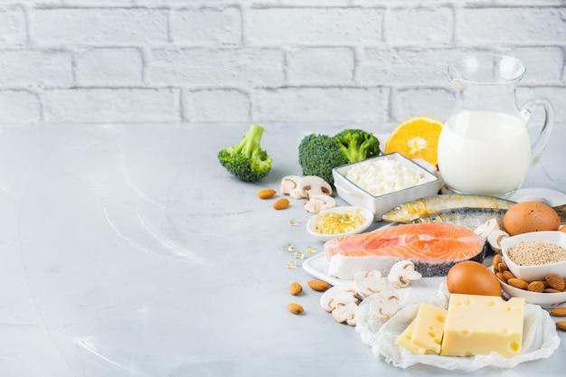Ausgewogene ernährung, gesundes ernährungskonzept. auswahl an nahrungsquellen reich an vitamin d und kalzium, lachs, milchprodukte, sardinen, brokkoli auf einem küchentisch. raumhintergrund kopieren