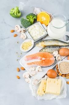 Ausgewogene ernährung, gesundes ernährungskonzept. auswahl an vitamin d und kalzium reichen nahrungsquellen, lachs, milchprodukte, sardinen, brokkoli auf einem küchentisch