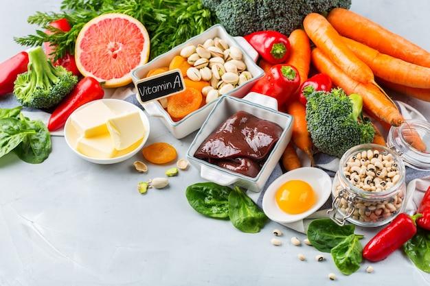 Ausgewogene ernährung, gesundes, sauberes esskonzept. auswahl an vitamin-a-reichen nahrungsquellen auf dem küchentisch